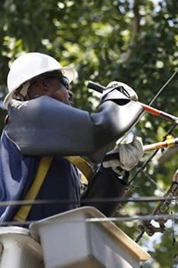 An electrical worker cuts a damaged overhead power line during emergency repairs in Wheaton